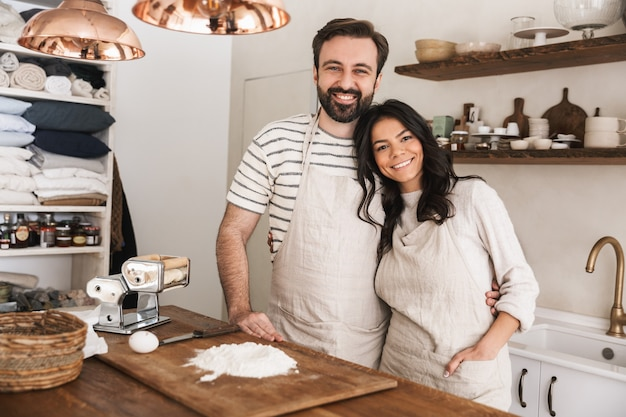 Portrait of happy couple man and woman 30s wearing aprons cooking pastry with flour and eggs in kitchen at home