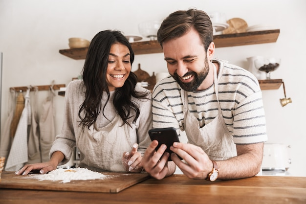 Portrait of happy couple man and woman 30s wearing aprons reading recipe while cooking pastry with flour and eggs in kitchen at home