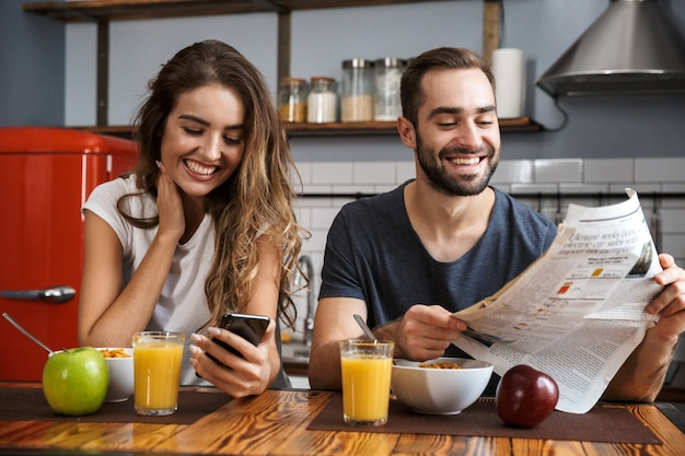 Portrait of happy couple man and woman sitting at table in kitchen while having breakfast at home in the morning