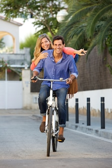 Portrait of happy couple riding bicycle together on path