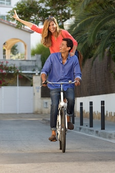 Portrait of happy couple riding bike together on path