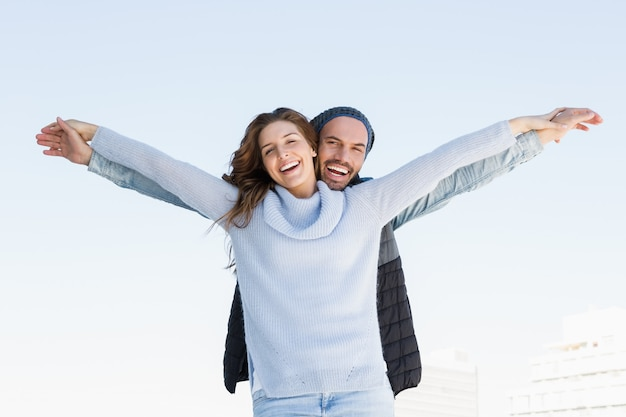 Portrait of happy couple standing with arms outstretched