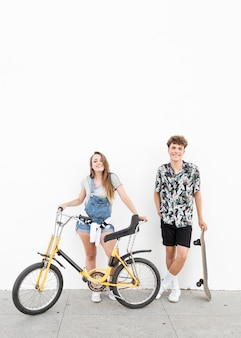 Portrait of a happy couple standing with bicycle and skateboard in front of wall