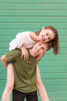 Portrait of a happy couple on a turquoise, a young man raised the girl on her back