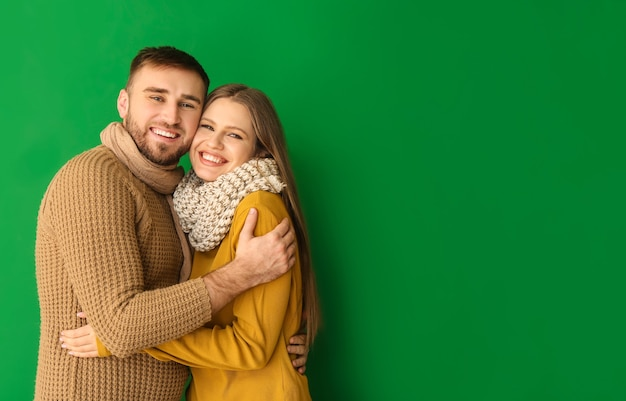 Portrait of happy couple in winter clothes on color surface