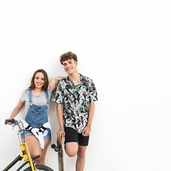 Portrait of a happy couple with bicycle and skateboard