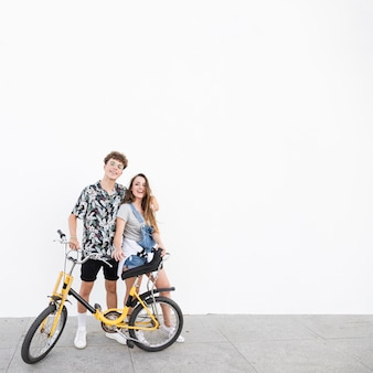Portrait of a happy couple with bicycle standing on sidewalk