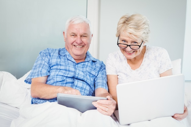 Portrait of happy couple with technologies