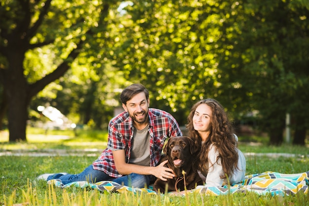 Portrait of a happy couple with their dog in park
