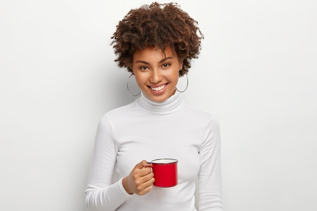 Portrait of happy curly haired woman with toothy smile, holds red mug of hot drink, looks straightly at camera