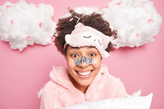 Portrait of happy curly haired young woman applies blackheads removal path on nose smiles broadly undergoes beauty skin care procedures dressed in pajama poses with pillow and flying feathers around