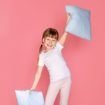 Portrait of a happy cute 5-6 year old baby girl hugging her soft pillow, enjoy the weekend, feel comfortable, get to bed, put on white sleepwear isolated over a pink background