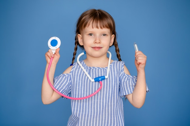 Portrait of a happy cute girl 5-6 years old with a stethoscope with in hands. the child plays a doctor.
