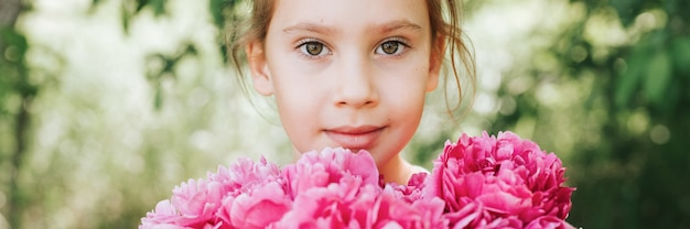 Portrait of a happy cute little caucasian seven year old kid girl, holds in hands a bouquet of pink peony flowers in full bloom on the green background of nature. banner