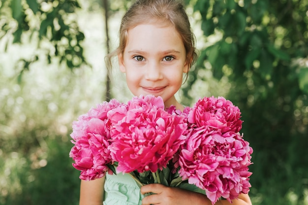 Portrait of a happy cute little caucasian seven year old kid girl, holds in hands a bouquet of pink peony flowers in full bloom on the green background of nature
