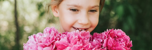 Portrait of a happy cute little caucasian seven year old kid girl, holds in hands and smell and enjoying a bouquet of pink peony flowers in full bloom on the background of nature. banner