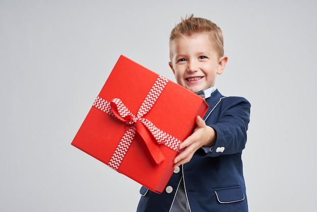 Portrait of a happy cute little kid holding gift box and looking at camera isolated over gray background