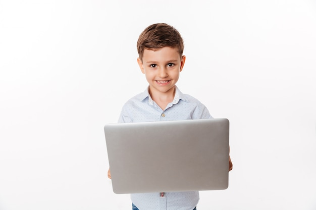 Portrait of a happy cute little kid holding laptop computer