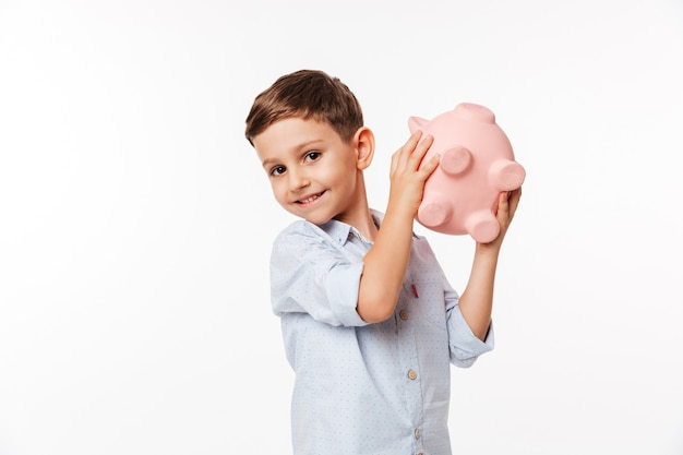 Portrait of a happy cute little kid holding piggy bank