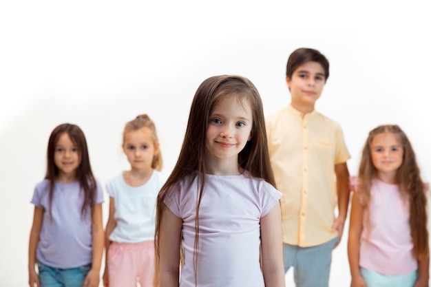 The portrait of happy cute little kids boy and girls in stylish casual clothes looking at camera against white wall
