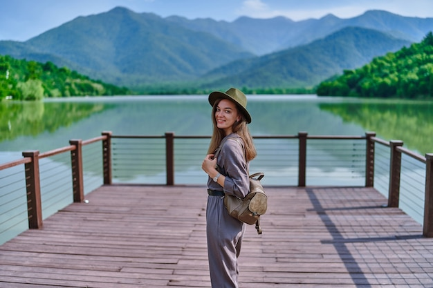 Portrait of happy cute smiling attractive wanderer girl wearing hat and backpack standing alone on pier with lake and mountains view. enjoying serene quiet peaceful atmosphere in nature