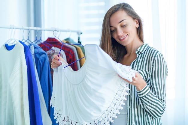 肖像画幸せなかわいい若いモダンなブルネットの女性の服のショールームで服の買い物中にトレンディなスタイリッシュな服を選ぶ