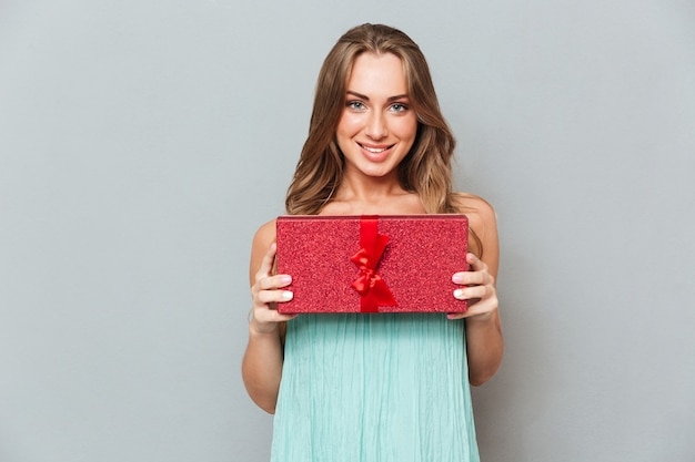 Portrait of happy cute young woman with gift box over gray wall