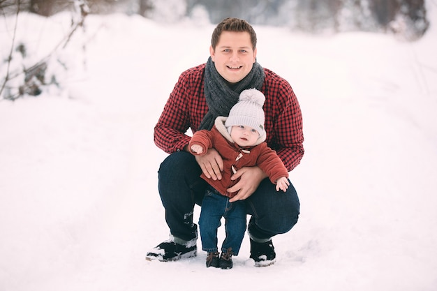 Portrait of happy dad with baby son while having fun in winter forest, copy space