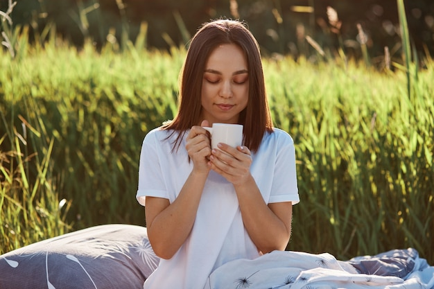 Portrait of happy dark haired female wearing white casual t shirt, holding cup of hot coffee or tee, enjoying drinking beverage in morning in green field, keeps eyes closed.