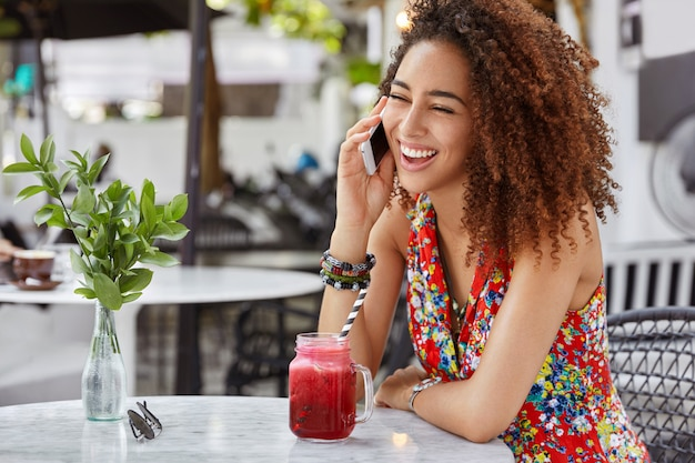 Portrait of happy dark skinned female with dark skin laughs sincerely while communicates with friend via smart phone, spends free time at coffee shop.