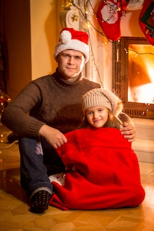 Portrait of happy daughter in santa bag sitting with father next to fireplace