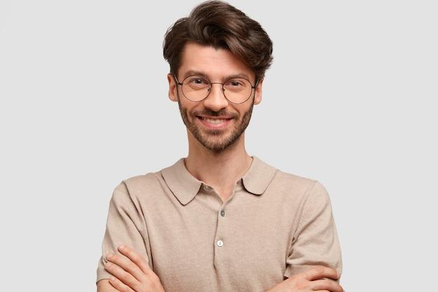 Ritratto di uomo attraente felice felice tiene le mani incrociate, vestito con un abbigliamento casual, guarda con gioia, essendo sicuro di sé nel successo, isolato sopra il muro bianco