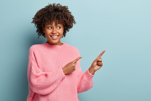 Portrait of happy delighted woman points in right direction on copy space, gazes happily, advertises nice product, wears oversized pink jumper, isolated on blue wall. check out cool advert there