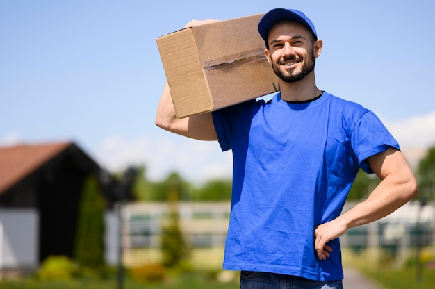 Portrait of happy delivery man carrying parcel