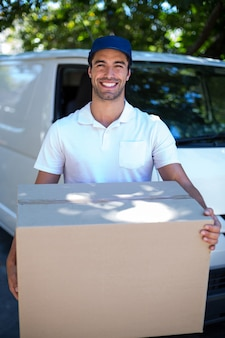 Portrait of happy delivery man holding cardboard box