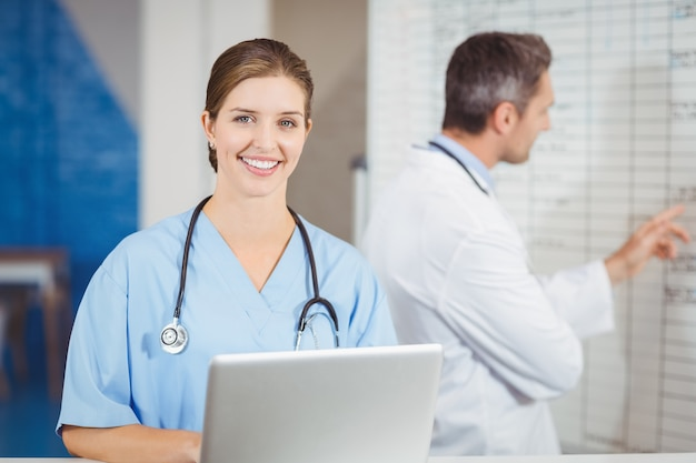 Portrait of happy doctor working on laptop with colleague pointing at chart