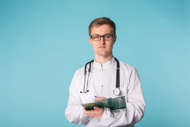 Portrait of happy doctor writing on clipboard against a blue background