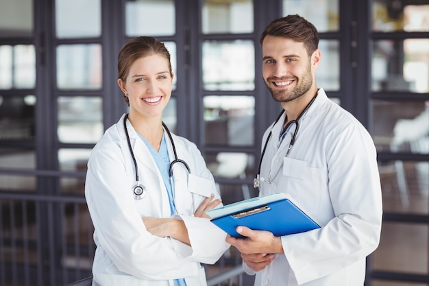 Portrait of happy doctors with clipboard