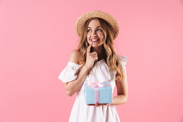 Portrait of happy dreamy woman wearing straw hat looking aside and holding present box isolated over pink wall