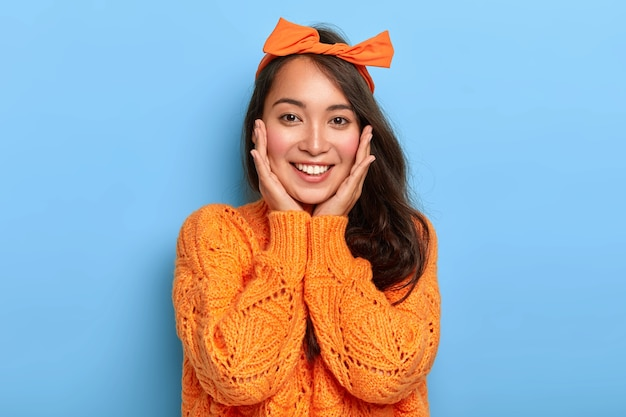Portrait of happy eastern woman touches both cheeks gently, has tender smile, shows white teeth, wears orange headband and sweater