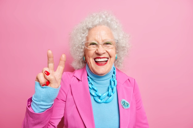 Portrait of happy elderly european woman with curly hair makes peace gesture has fun wears bright makeup dressed in fashionable clothes
