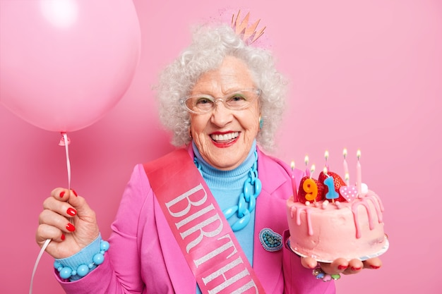 Portrait of happy elderly woman has grey curly woman enjoys festive event holds cake with burning candles inflated balloon wears fashionable clothes spends free time on bday party. holiday concept