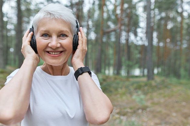 Portrait of happy energetic middle aged woman listening to music while jogging outdoors, holding hands on headphones