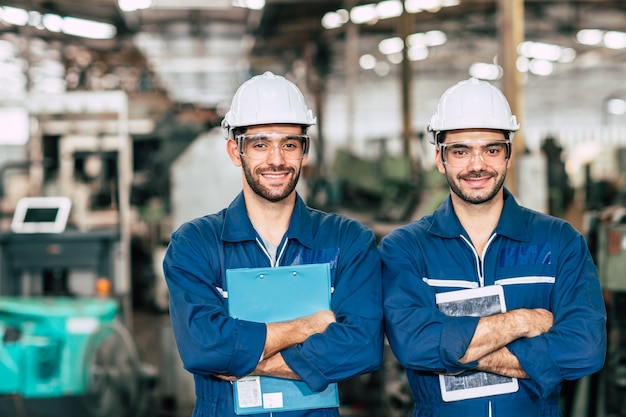 Portrait of happy engineer team smiling worker working together in industry factory.