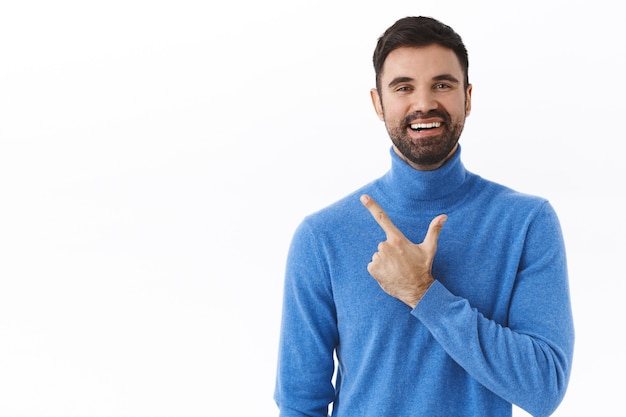 Portrait of happy, enthusiastic male entrepreneur, bearded guy pointing finger left and smiling as inviting check-out, click link, showing way recommend product, white wall