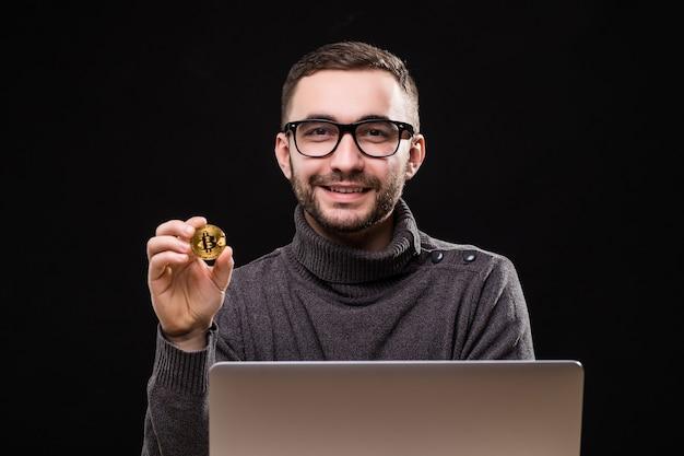 Ritratto di un imprenditore felice che mostra bitcoin mentre è seduto alla scrivania con computer portatile isolato su nero