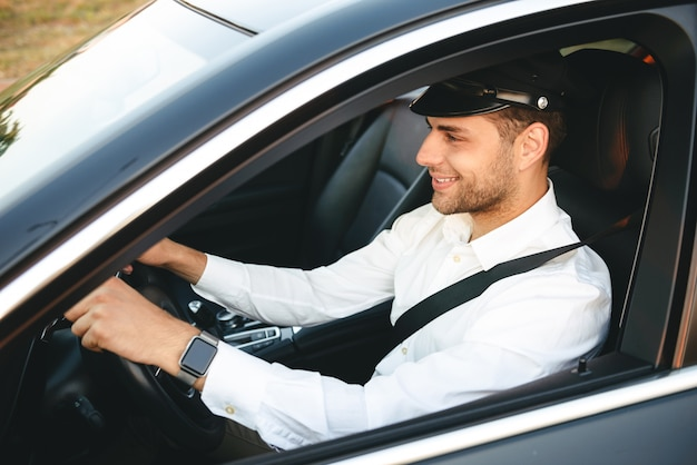 Portrait of happy european man taxi driver wearing uniform and cap, driving car fastening seat belt