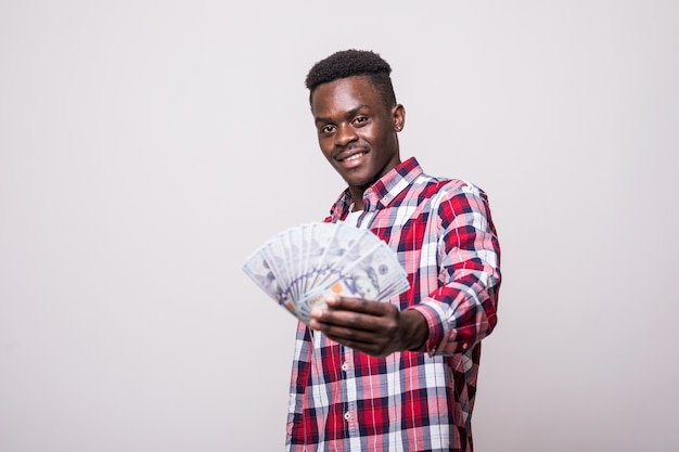 Portrait of a happy excited african man holding bunch of money banknotes and looking isolated