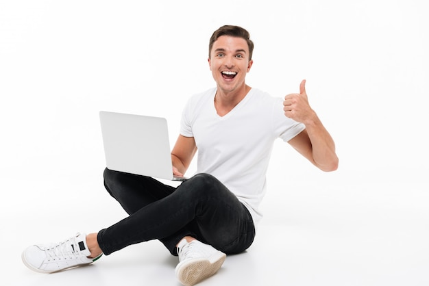 Portrait of a happy excited man holding laptop computer