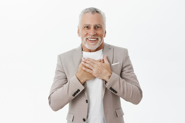 Portrait of happy excited senior man looking flattered and amazed, holding hands over chest